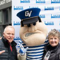 Two alumni pose with Louie the Laker